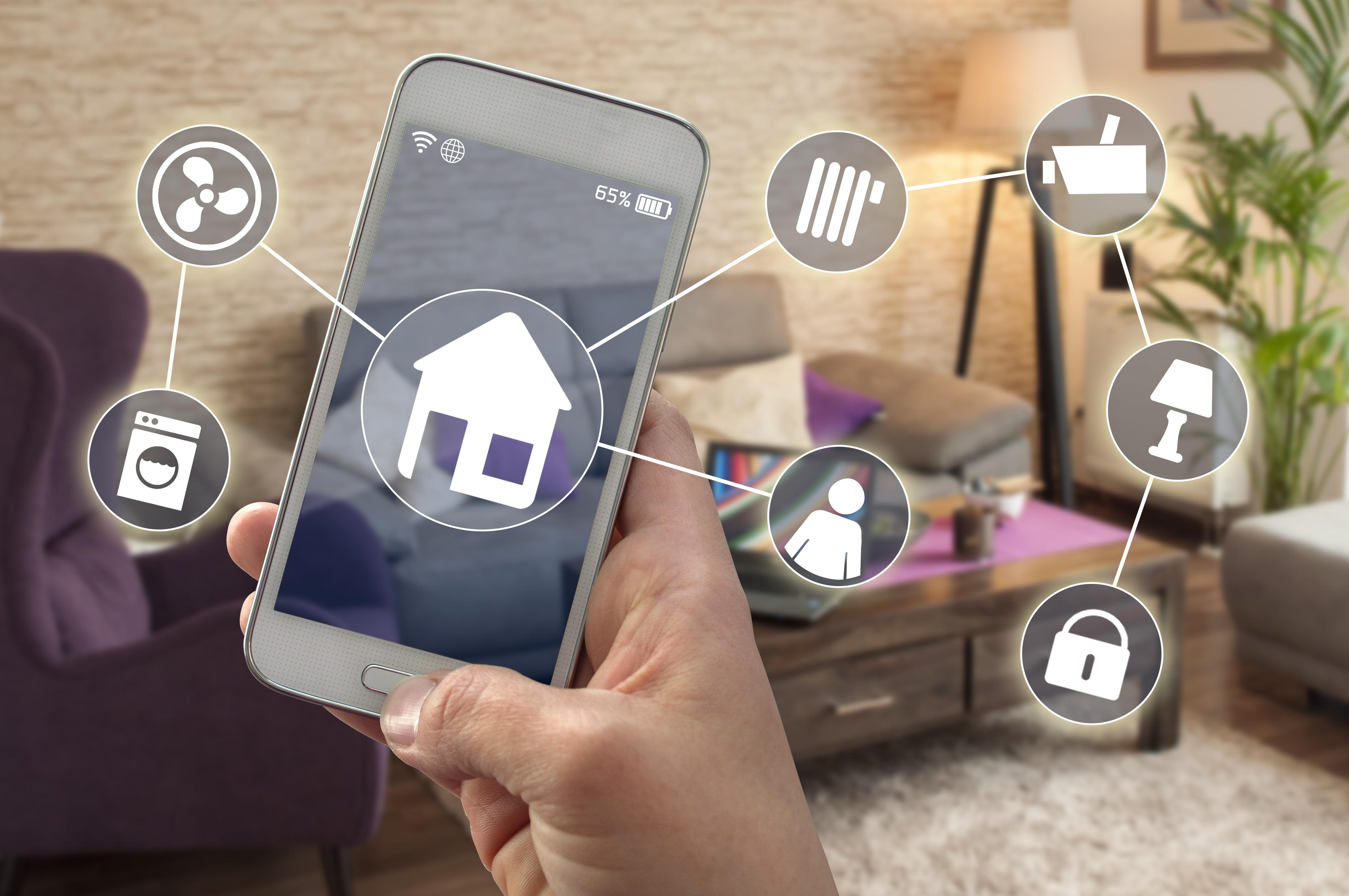 Smartphone in einem Wohnzimmer mit Icons für Haus, Waschmashine Heizung, Ventilator usw.