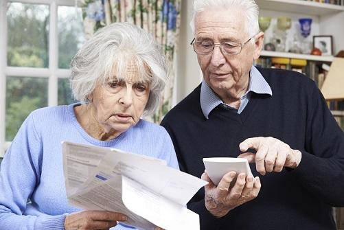 Ehepaar mit Taschenrechner und Rechnungen