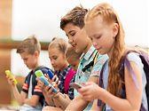 mehrere Kinder die auf ihre Smartphones schauen